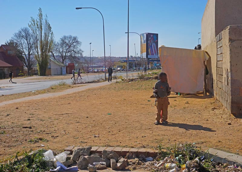 Barefoot kids hugging on the street corner, Soweto.