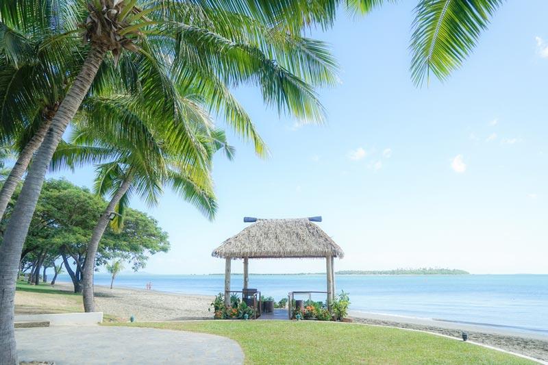 Best travel insurance for prengancy. Babymoon idea Denarau Island Fiji. Palm trees and beach hut at Denarau Island
